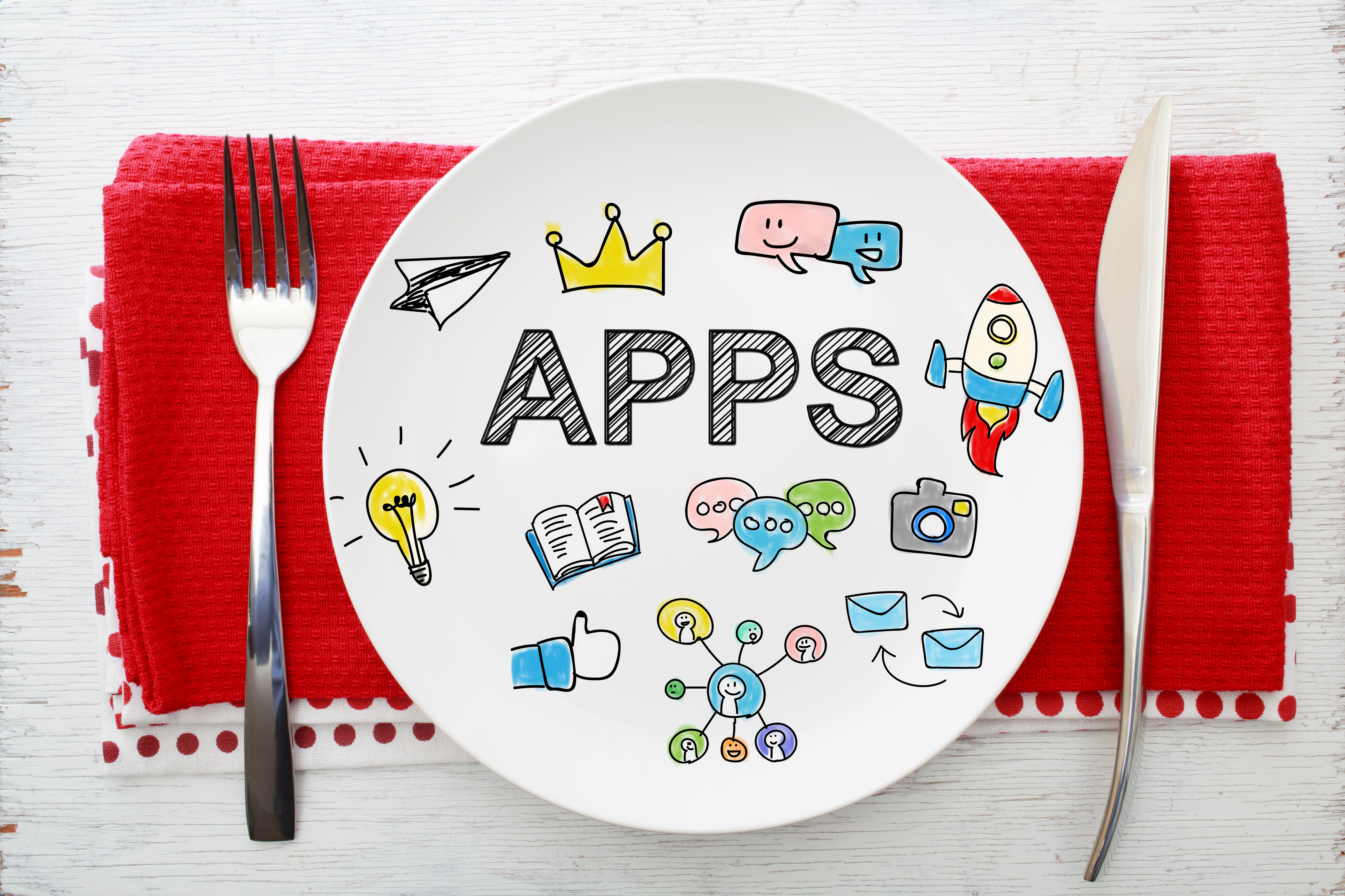 Apps concept on white plate with fork and knife on red napkins